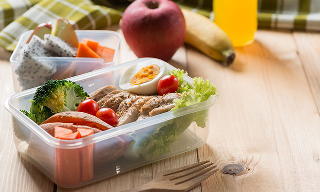 Healthy lunch boxes in plastic package, Grilled chicken breast with sweet potato, egg and vegetable salad, fruit, orange juice. Diet food concept.