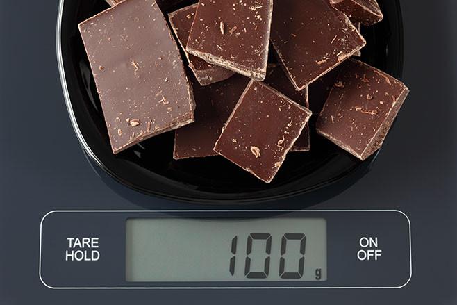 Broken dark chocolate in a black plate on digital scale displaying 100 gram.