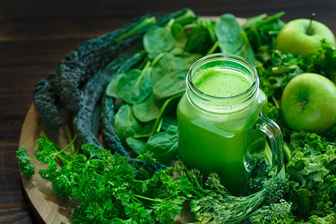Variety of Organic Leafy Greens with a Glass Jar of Fresh Juice