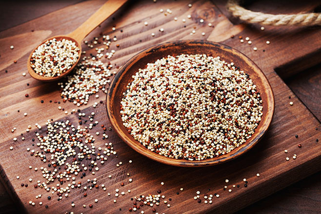Mixed quinoa in bowl on wooden kitchen board.