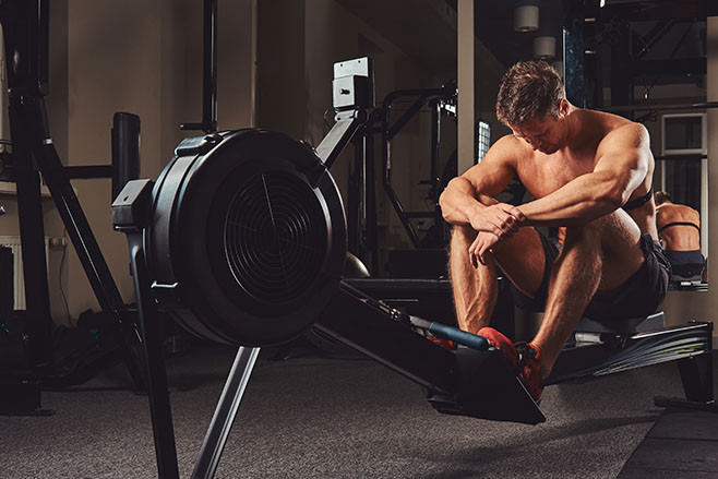 A muscular shirtless athlete resting after a hard workout while sits on the rowing machine in the gym.