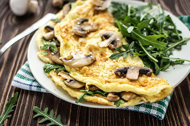 Omelette with mushrooms and arugula on a wooden background