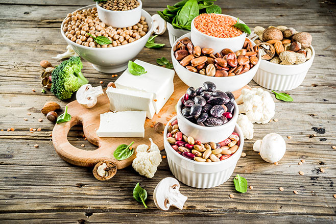 Healthy plant vegan food, veggie protein sources: Tofu, vegan milk, beans, lentils, nuts, soy milk, spinach and seeds. Old wooden background copy space