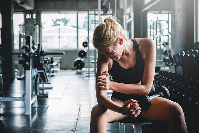 Woman have accident injury and hurt at arms while workout and weight training at gym, muscle pain concept