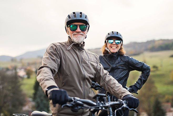 An active senior couple with helmets and electrobikes standing outdoors on a road in nature.