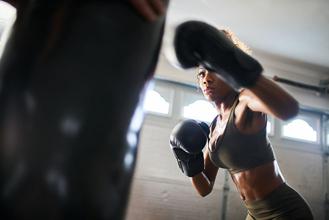 african american woman striking punching bag in home gym