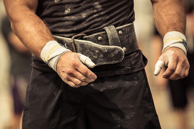 Closeup portrait of a bodybuilder girding on his bodybuilding belt