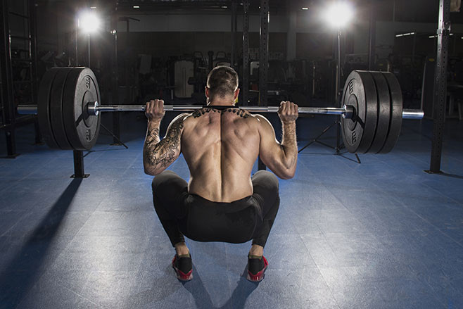 Attractive muscular shirtless bodybuilder doing heavy squat exercise in modern fitness center.Functional training.Back view.