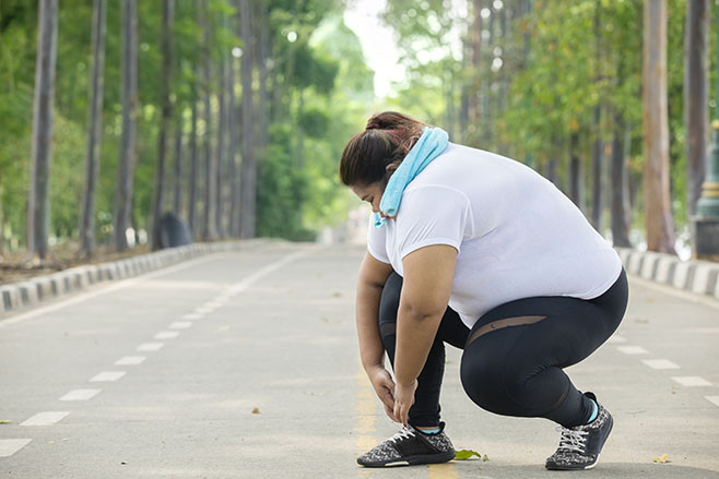 Picture of fat woman tying her shoelaces before doing jogging exercises on the road