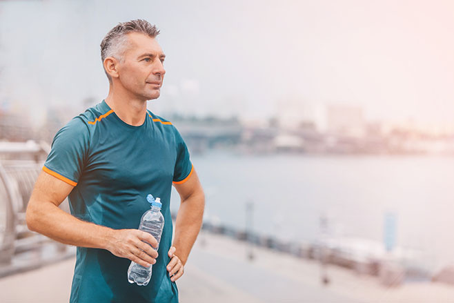 Portrait of healthy athletic middle aged man with fit body holding bottle of refreshing water, resting after workout or running. middle aged male with a drink after outdoor training.