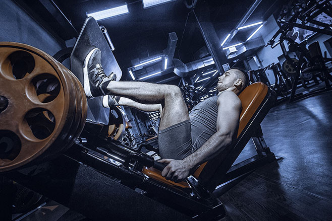 Man Using A Press Machine In A Fitness Club. Toned image. Man doing an exercise on its legs in the simulator. side view