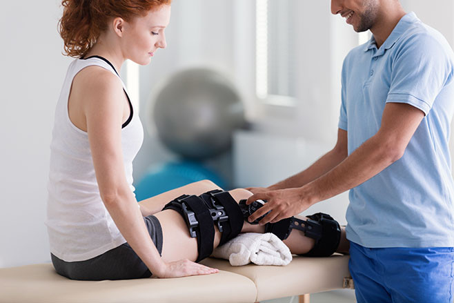 Smiling professional physiotherapist taking care of patient with leg injury