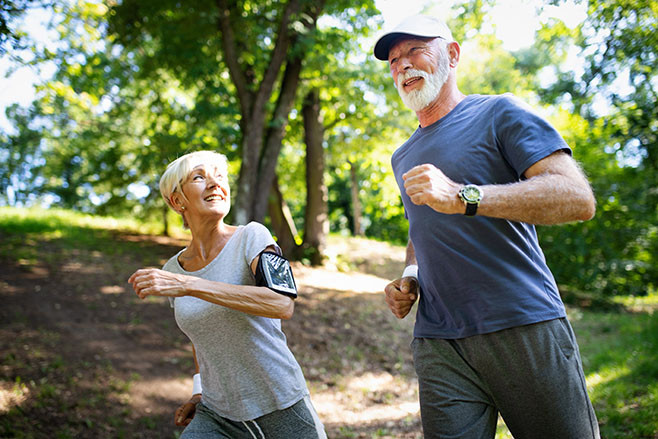 Mature or senior couple doing sport outdoors, running in a park