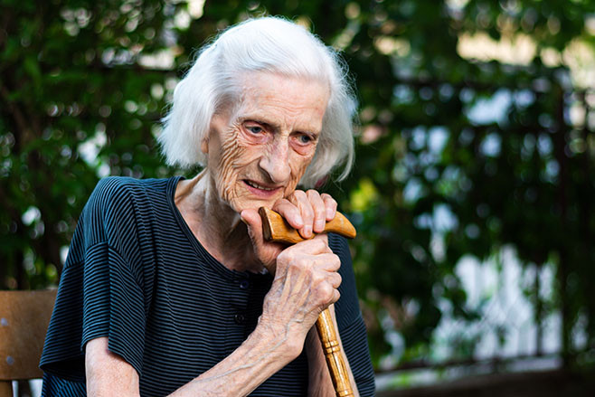 Portrait of a senior woman with a walking cane outdoors