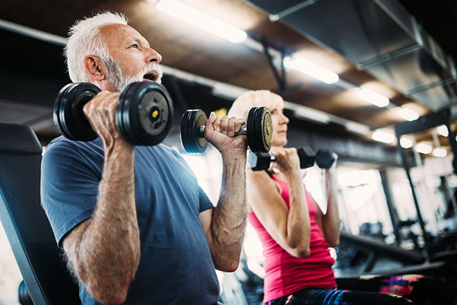 Happy mature people doing exercises in gym to stay fit