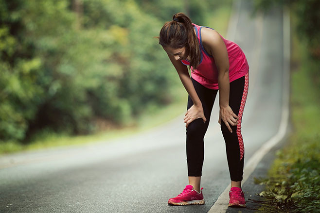 Woman is tired from jogging on a steep slope