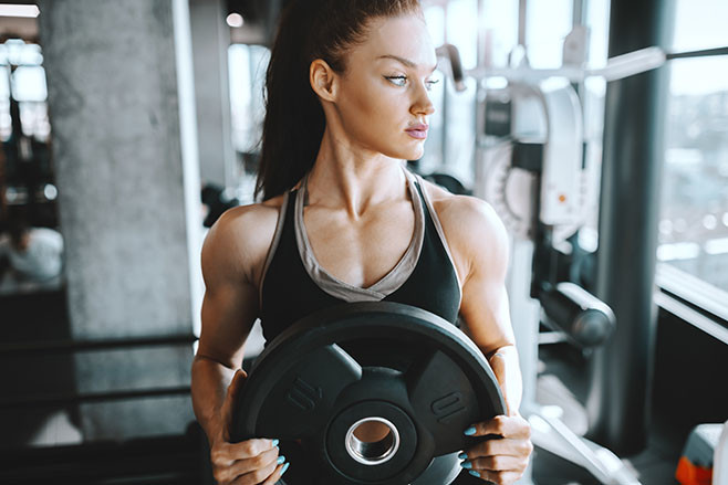 Young attractive Caucasian female bodybuilder with ponytail holding weight plate and looking away while standing in gym next to window. Don't wish for it, work for it.
