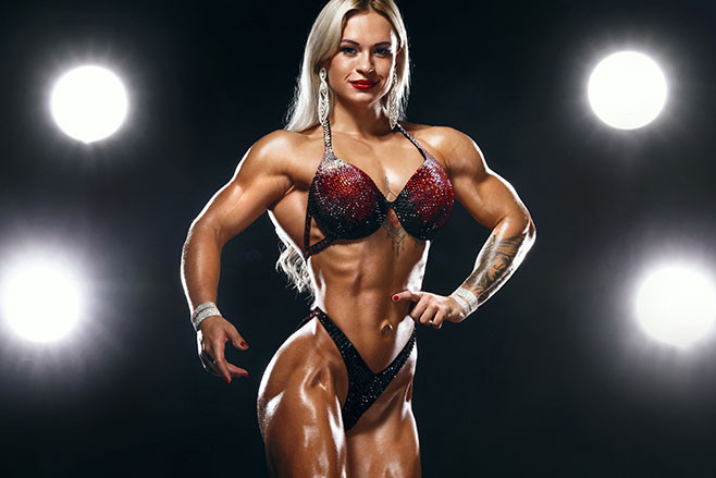 Young strong woman bodybuilder on background with lights.