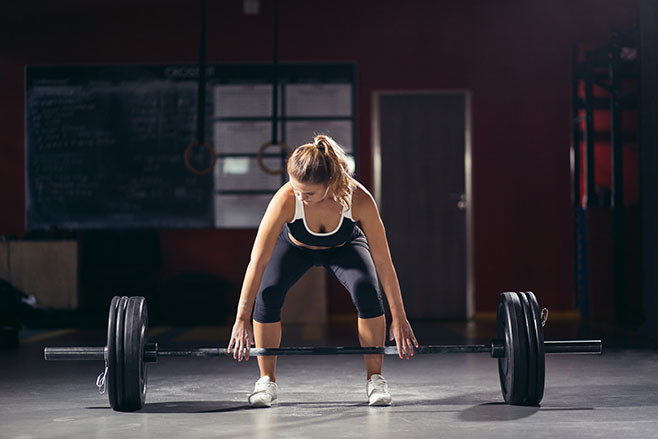 Intense workout in dark gym: young athletic woman doing deadlift with barbell on standing position, legs at shoulder level.
