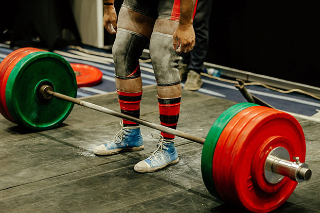 powerlifter legs in gym chalk and knee sleeves competition deadlift