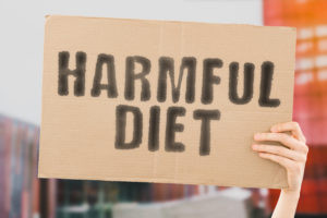 """The phrase """" Harmful diet """" on a banner in men's hand with blurred background. Healthcare. Dangerous. Nutrition. Life. Essential. Hazardous"""